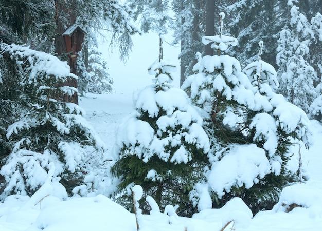 Winterbos met besneeuwde sparren en de kruisiging van jezus christus op stam (oostenrijk).