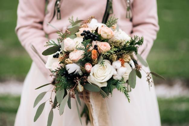 Winterbruidsboeket met rozen, katoen, spar, veren, gedroogde bloemen in de handen van de bruid