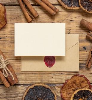Wintercompositie met een blanco kaart en verzegelde envelop kruiden en gedroogde vruchten op houten tafel
