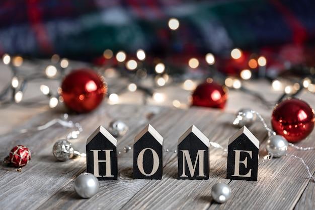 Wintercompositie met het decoratieve woord huis en kerstballen op een onscherpe achtergrond met bokeh.