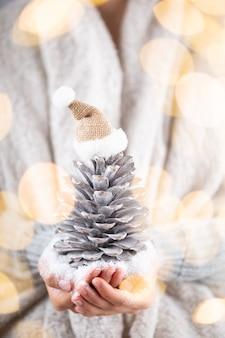 Winterconcept jonge handen met kerstdecor. idee voor kerstversiering. kerstdecor in de handen van een vrouw, achtergrond met gouden bokeh.