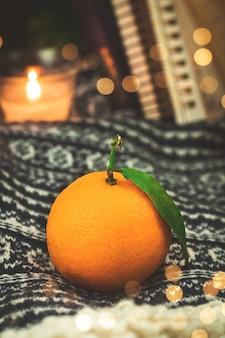 Winterconcept met mandarijnen of mandarijnen, stilleven gezellige compositie op gebreide trui achtergrond met bokeh. hoge kwaliteit foto