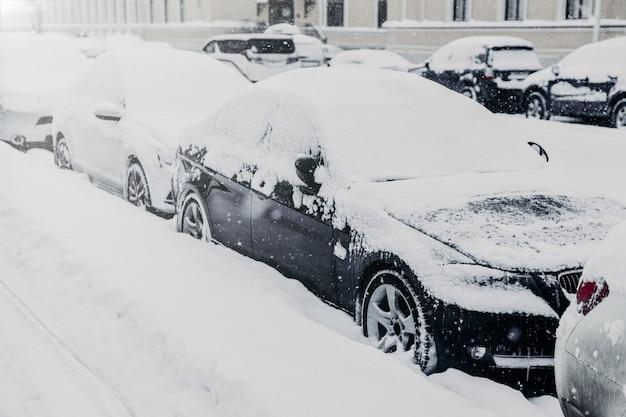 Winterdag in stedelijke omgeving. auto's staan op parkeerplaats, bedekt met witte sneeuw na zware sneeuwval