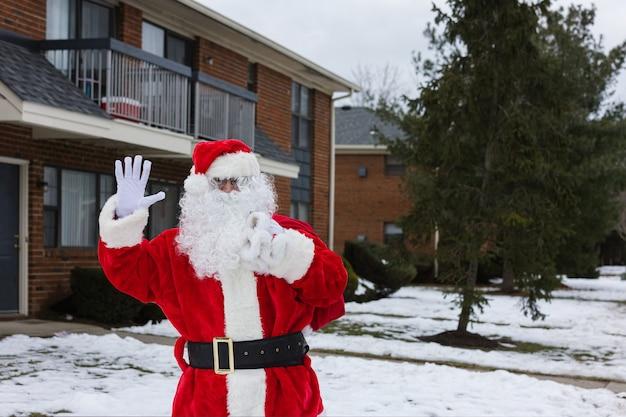 Winterdag santa claus arriveert van kerstcadeautjes buiten op huis