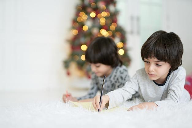 Winterdagen twee kleine latijns-jongens die foto's maken met kleurrijke potloden terwijl ze op liggen