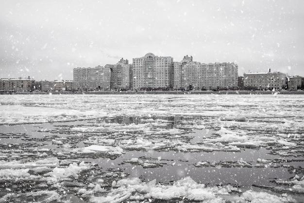 Winterijs drijft op de rivier. ijs op de rivier tegen stedelijke kustarchitectuur.