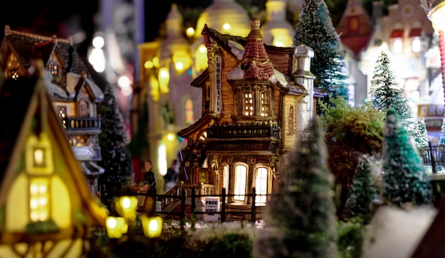 Winterkerstavondscène met traditionele miniatuurdorpshuizen. speelgoedhuis chocoladewinkel in kerstbomen in speelgoedstad met gloeiende ramen. vintage europese speelgoedstad.