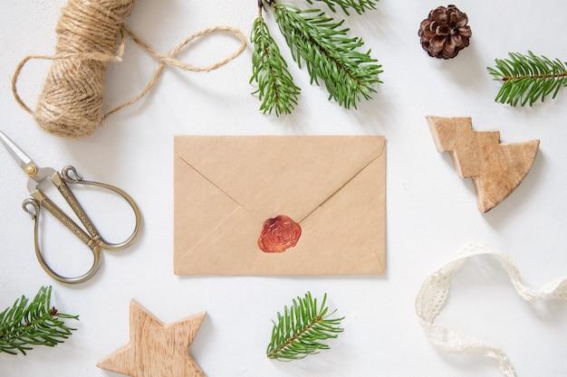 Winterkerstcompositie met een kaart over verzegelde envelop platliggend mockup