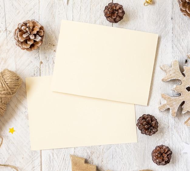 Winterkerstcompositie met kaarten plat. kerstmis en nieuwjaar wenskaartsjabloon met dennenappels, houten versieringen en touw op marmeren achtergrond bovenaanzicht. vakantiemodel.