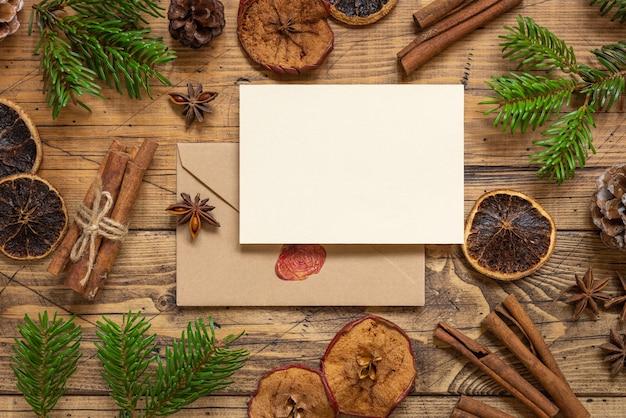 Winterkerstsamenstelling met een blanco kaart en envelop op een houten tafel plat gelegd