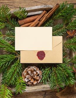 Winterkerstsamenstelling met een blanco kaart en verzegelde envelop op houten tafel. kerstmis en nieuwjaar wenskaartsjabloon met dennentakken en dennenappels bovenaanzicht. vakantiemodel