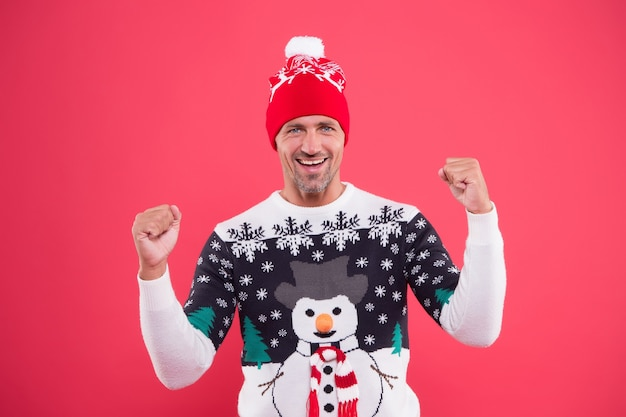 Winterkou wordt sterk. ongeschoren kerelglimlach in trui in sneeuwpop winterstijl. gelukkig man met casual winterlook. warm gebreid ontwerp voor koud weer. warm en feestelijk houden tijdens de wintervakantie.