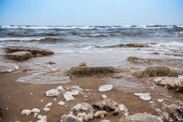Winterkoud oostzeestrand is besneeuwd en er zijn grote golven in de zee, in saulkrasti in letland