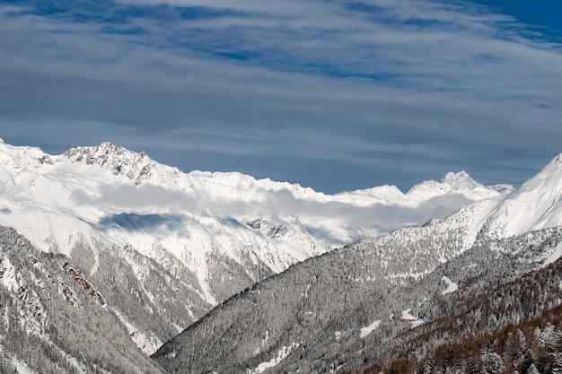Winterlandschap; bovenaanzicht van skigebied met blauwe lucht en ijzige pijnbomen vallende sneeuw.