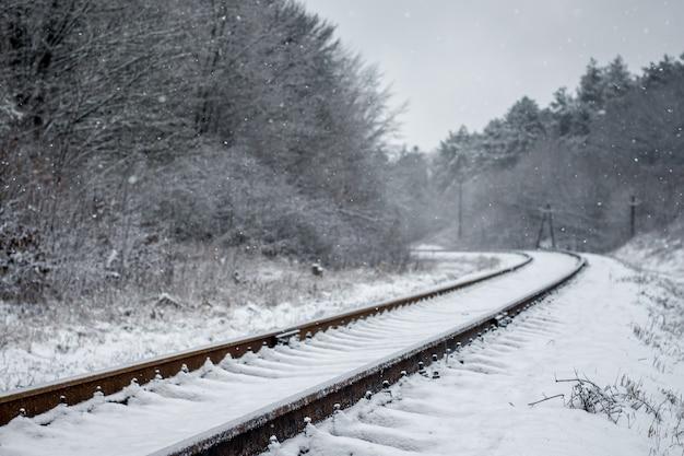 Winterlandschap, de spoorlijn gaat in de verte, aan de zijkanten - het bos_