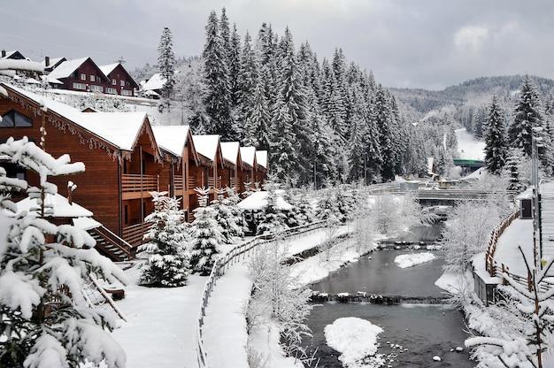 Winterlandschap. houten huisjes vakantiehuizen in vakantieoord in de bergen aan de oever van een bergrivier.