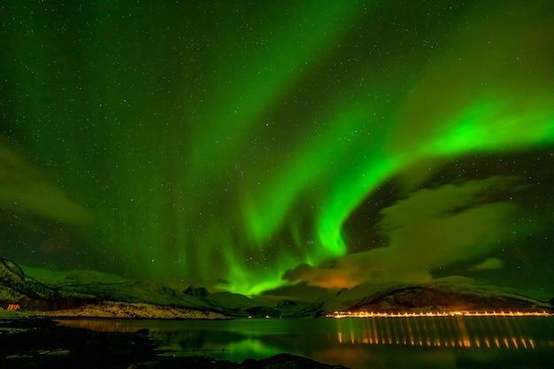 Winterlandschap met aurora, zee met hemel reflectie en besneeuwde bergen. natuur, lofoten aurora borealis.