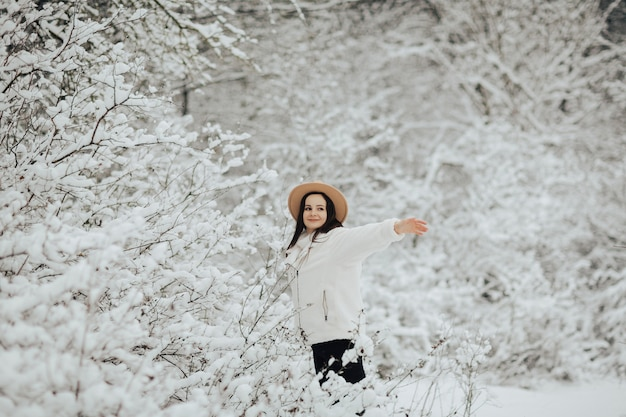Winterlandschap met besneeuwde bomen. gelukkig meisje permanent in de buurt van besneeuwde bomen in het bos.
