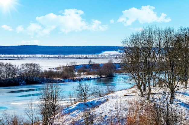 Winterlandschap met besneeuwde bossen, rivieren en velden bij zonnig weer