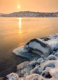 Winterlandschap met besneeuwde stenen aan de prachtige rivier