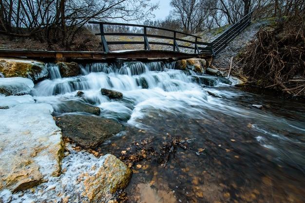 Winterlandschap met bevroren rivier, waterval en een brug