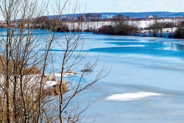 Winterlandschap met bomen aan de rivier bij zonnig weer