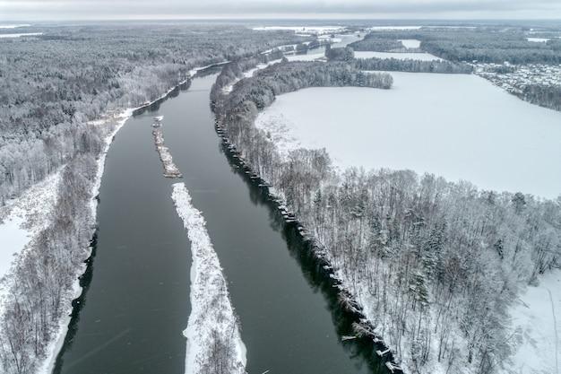 Winterlandschap met een rivier die door het winterbos stroomt.