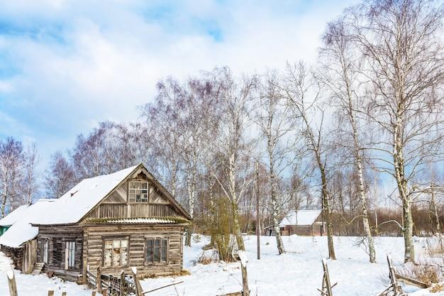 Winterlandschap met oude houten huis en bomen met blauwe bewolkte hemel,