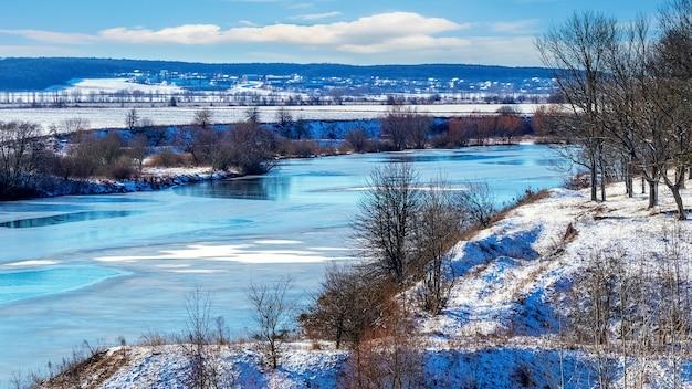 Winterlandschap met rivier en bomen op de rotsen