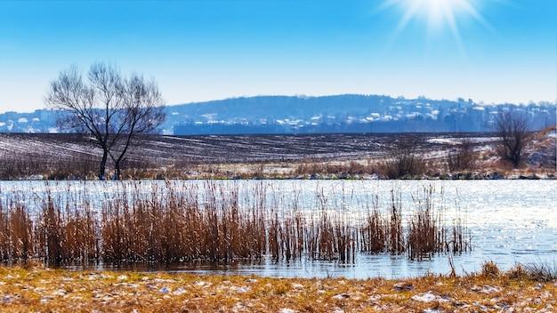 Winterlandschap met rivier en veld bij zonnig weer