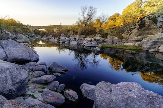 Winterlandschap met rivier, reflecties in het water en grote rotsen. canencia. gredos.