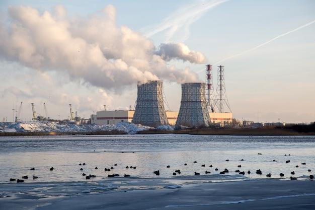 Winterlandschap met rokerige schoorstenen van thermische krachtcentrale