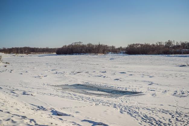 Winterlandschap met sneeuw bedekte winter rivier in ijzige dag