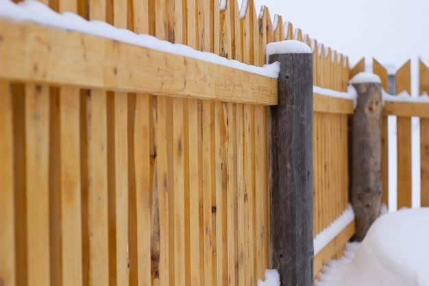 Winterlandschap op het hek. gebogen hek perspectief bekijken. houten dorpsgebouw.