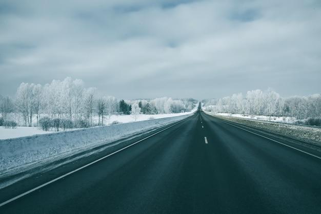 Winterlandschap, weg, spoor tussen witte driften, heuvels en bomen met rijm