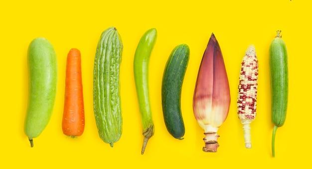 Wintermeloen, wortel, bittere meloen, groene lange aubergine, komkommer, bananenbloesem, rauwe maïs en sponspompoen op gele achtergrond. seks concept