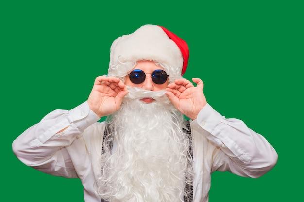 Wintermode en verkoop. portret van een knappe man met een kerstmuts, knipogen terwijl hij tegen een rode muur staat. de hipster houdt een bril vast en kijkt naar de camera. plaats voor tekst.