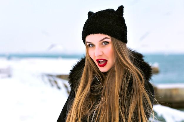 Wintermode portret van sensuele blonde vrouw, rode volle lippen, veel sneeuw, grappige hoed, elegante jas, winterreisexpeditie, lange haren, winderig weer, geweldige ijskust.