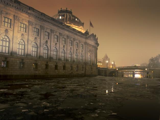 Winternachtlandschap in berlijn met beroemd bode-museum en gebarsten ijsblokken in de rivier de spreee