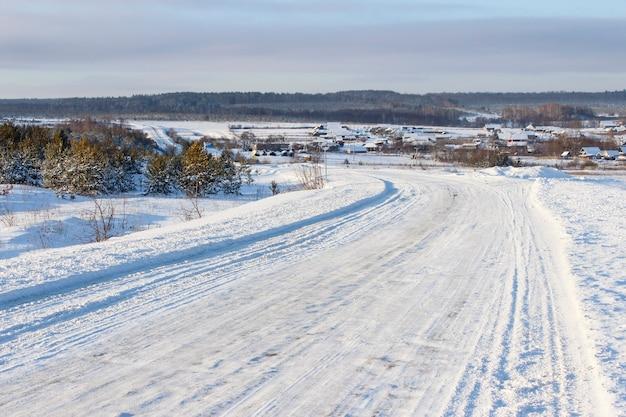 Winterpad met steile bochten en heuvels, langs het dorp.