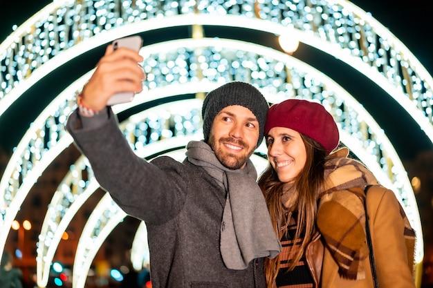 Winterportret van een kaukasisch koppel dat geniet van de kerstverlichting van de stad en een selfie maakt met de mobiel voor sociale netwerken