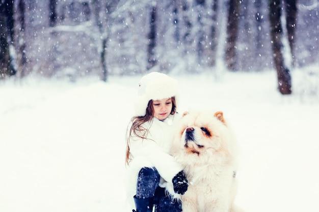 Winterportret van een klein meisje en een chow-chowhond in het bos