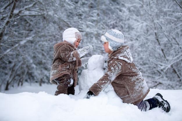 Winterpret broers spelen in de sneeuw en maken een sneeuwpop