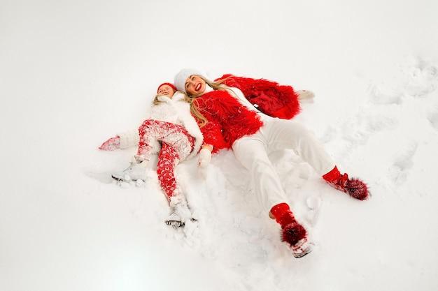 Winterpret. jonge mooie blonde moeder met lang haar ligt in de sneeuw met haar mooie dochter en lacht. sneeuwengel. twee blondines in mooie winterkleren in de sneeuw.