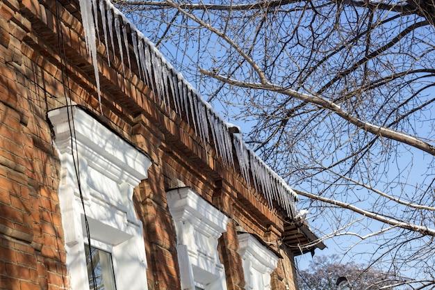 Winters dak van het huis met ijspegels
