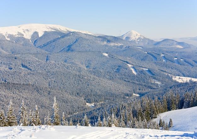Winters rustig berglandschap met rijp en besneeuwde sparrenbomen en alpine skipistes in een bos
