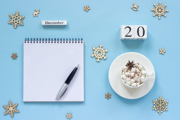 Winterse samenstelling. houten kalender 20 december kopje cacao met marshmallow en steranijs, lege open kladblok met pen en sneeuwvlok op blauwe achtergrond. bovenaanzicht platliggend mockup concept