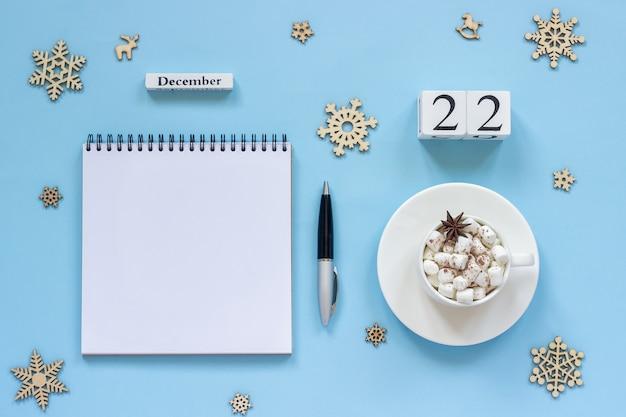 Winterse samenstelling. houten kalender 22 december kopje cacao met marshmallow en steranijs, lege open kladblok met pen en sneeuwvlok op blauwe achtergrond. bovenaanzicht platliggend mockup concept