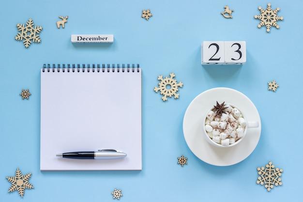 Winterse samenstelling. houten kalender 23 december kopje cacao met marshmallow en steranijs, lege open kladblok met pen en sneeuwvlok op blauwe achtergrond. bovenaanzicht platliggend mockup concept