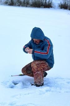 Winterseizoen oude man vissen op een meer